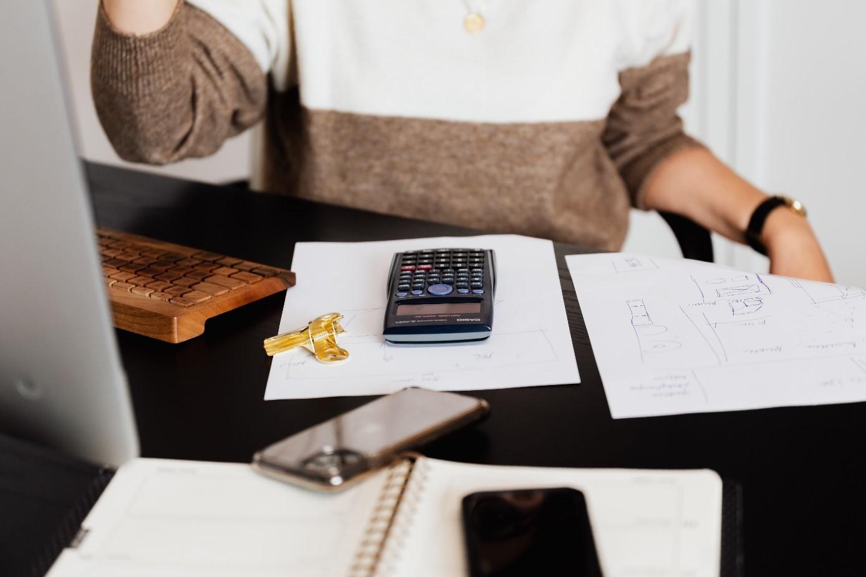 Kobieta przy biurku używa kalkulatora