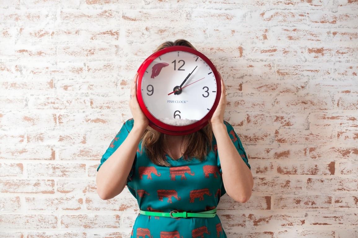 Kobieta w trzyma zegar na wysokości głowy, zasłaniając twarz